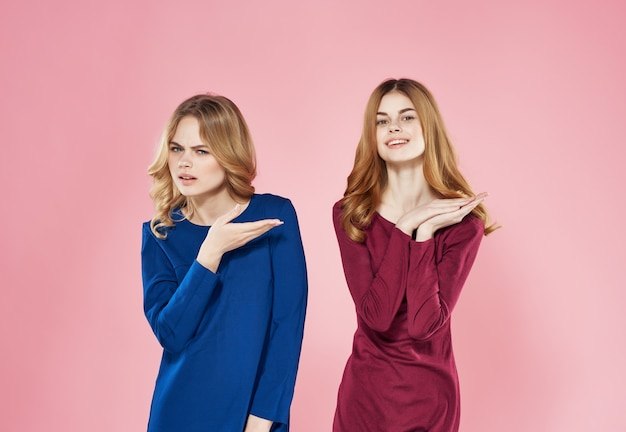 Cute girlfriends in dresses are standing side by side on a pink background model