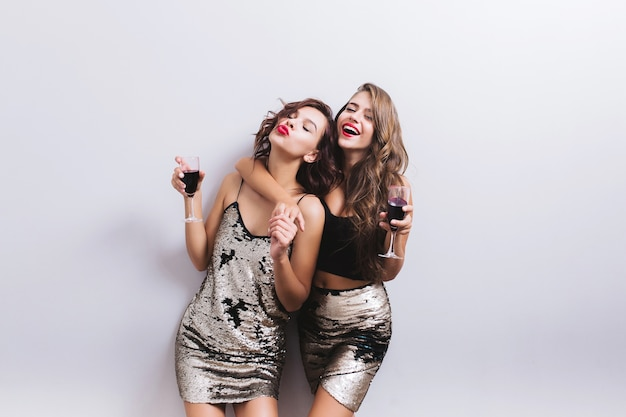 Cute girls, cheerful best friends, sisters enjoying party, having fun, hugging with glasses of red wine. wearing bright dresses with spangles, stylish sexy look, beautiful wavy hair. isolated.