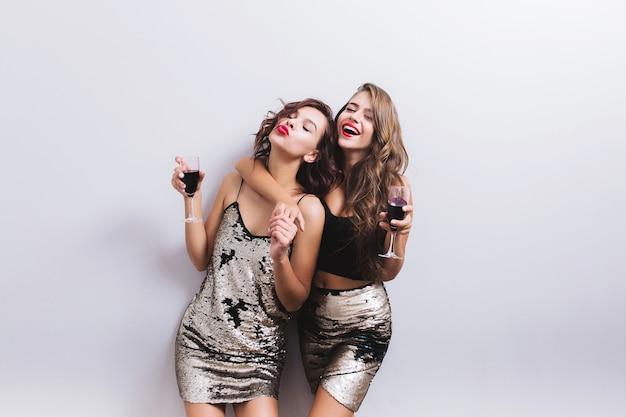 Ragazze carine, migliori amiche allegre, sorelle che godono della festa, che si divertono, che si abbracciano con bicchieri di vino rosso. indossare abiti luminosi con lustrini, look sexy ed elegante, bei capelli mossi. isolato.