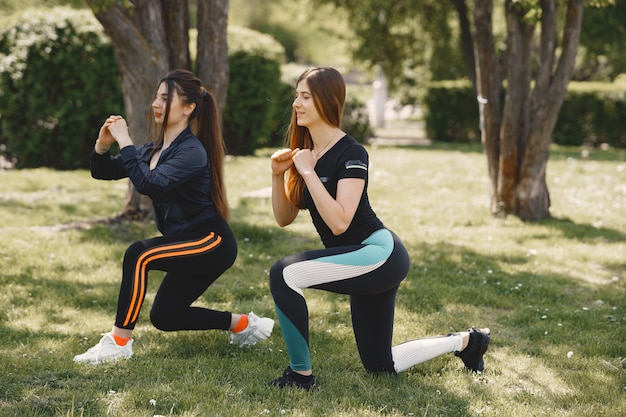 Cute girls doing yoga in a summer park