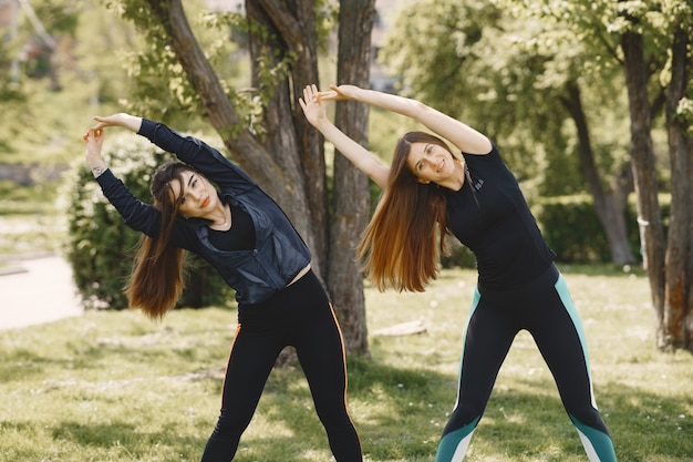 Ragazze sveglie che fanno yoga in un parco di estate
