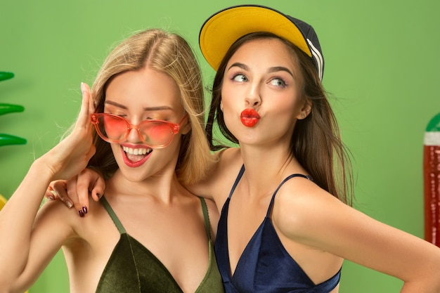 스튜디오에서 포즈를 취하는 수영복에 귀여운 소녀. 녹색 배경에 여름 초상화 백인 청소년입니다.
