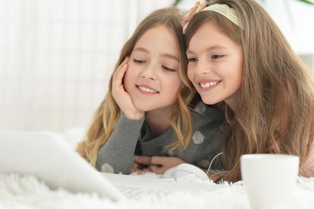 自宅でノートパソコンを持っているかわいい女の子
