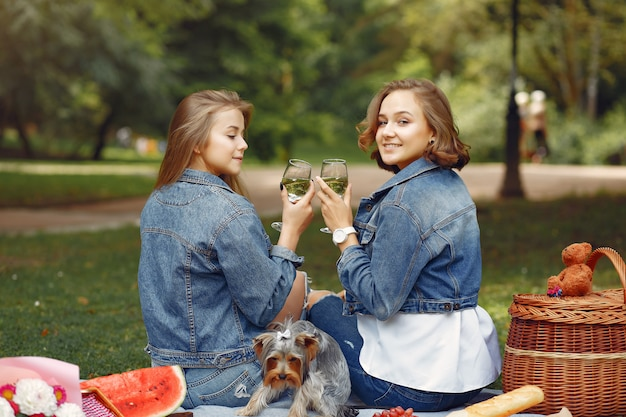 Cute girls in a park playing with little dog