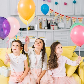 Cute girls sitting on sofa holding colorful balloons