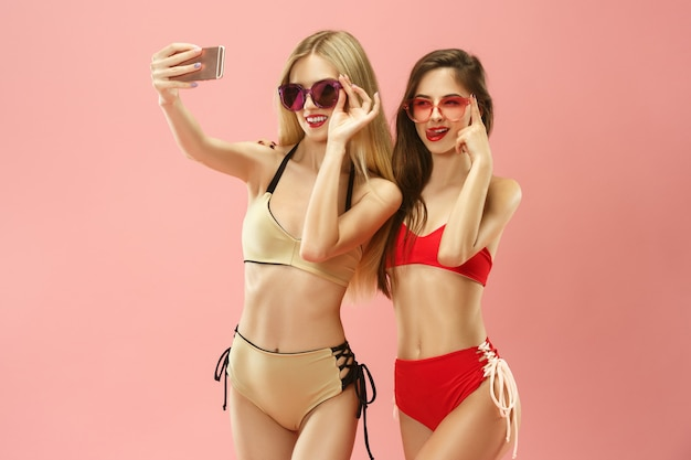 Cute girls in swimsuit posing and making photo selfie on mobile phone at studio.
