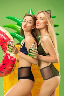 Cute girls in swimsuit posing at studio and drinking orange juice. summer portrait caucasian teenagers on a green background.