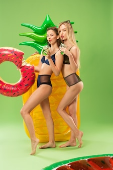 Cute girls in swimsuit posing at studio and drinking orange juice. summer portrait caucasian teenagers on green
