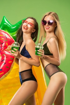 Cute girls in swimsuit posing at studio and drinking orange juice