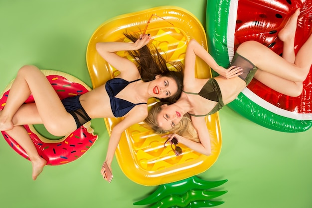 Cute girls in swimsuit posing at studio. summer portrait caucasian teenagers on a green background.