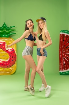 Cute girls in swimsuit posing at studio with inflatable swimming circle