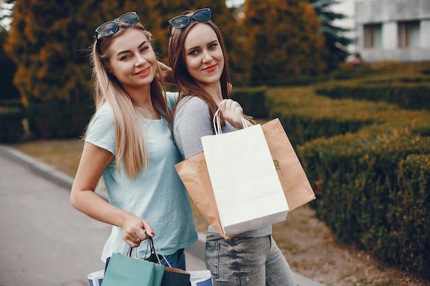도시에서 쇼핑 봉투와 함께 귀여운 여자
