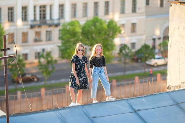 Милые девушки на крыше наслаждаются с видом на красивый закат в санкт-петербурге в россии