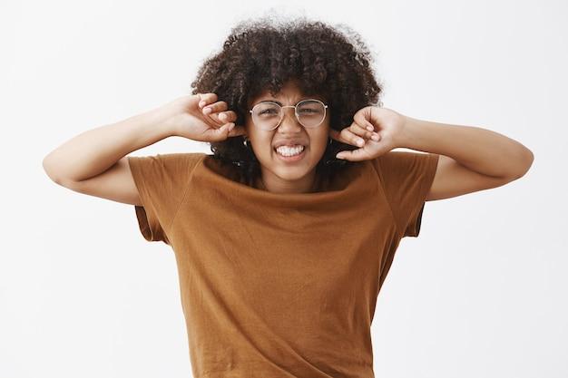 Nerd femmina carina di bell'aspetto con acconciatura afro in occhiali prescritti trasparenti accigliato e naso rugoso che stringe i denti per antipatia e disagio che copre le orecchie non sente rumori fastidiosi