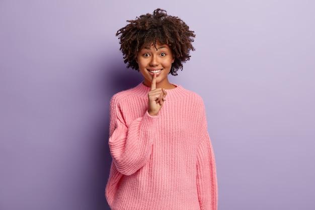 귀여운 잘 생긴 웃는 여자가 쉿하는 몸짓을하고, 개인 정보를 말하고, 부드럽게 미소 짓고, 니트 핑크 점퍼를 입습니다.