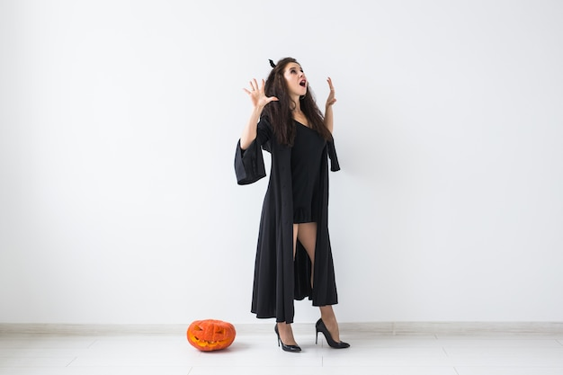 Cute gothic woman in halloween style clothes with pumpkin in hands over light background with copy space