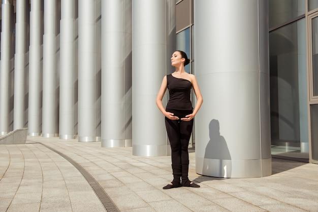 Милая изящная балерина стоит возле белой колонны