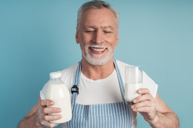Cute grandfather with gray hair and beard holds a bottle of milk and a glass, wears an apron