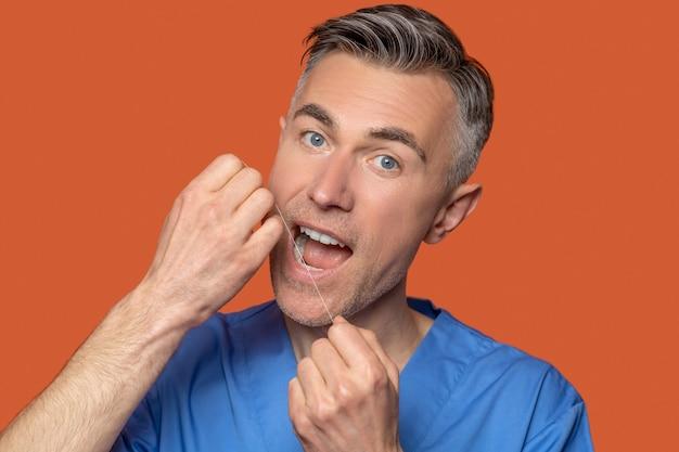 Cute gray-eyed man using dental floss