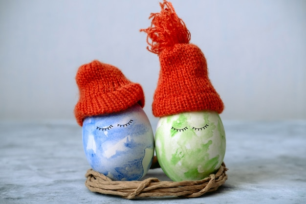 Cute green and blue easter in orange knitted hats
