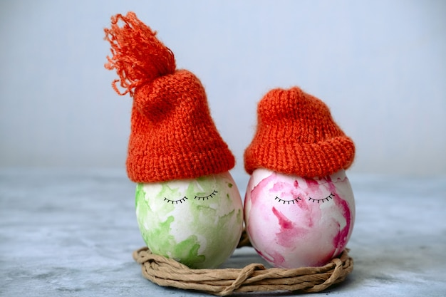 Cute green and pink easter in orange knitted hats