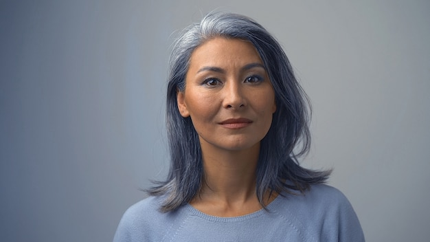 Cute grey-haired woman with a serious expression on her face