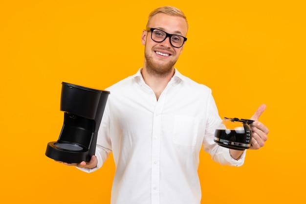 Симпатичный парень-консультант в белой рубашке держит кофемашину и кружку кофе на желтом