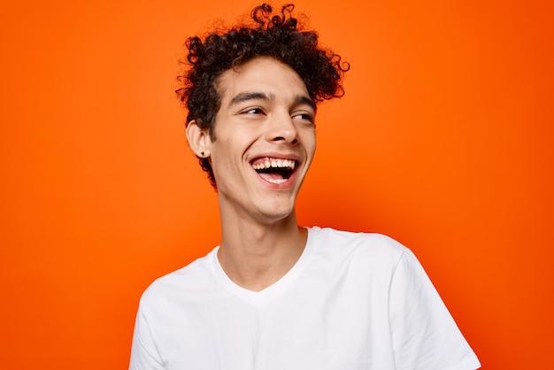白いtシャツと楽しい感情のクローズアップオレンジ色の背景のかわいい男