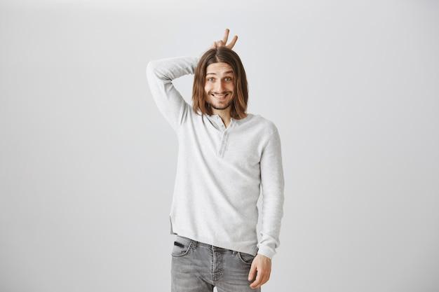 Симпатичный парень показывает рога на голове, будучи счастлив