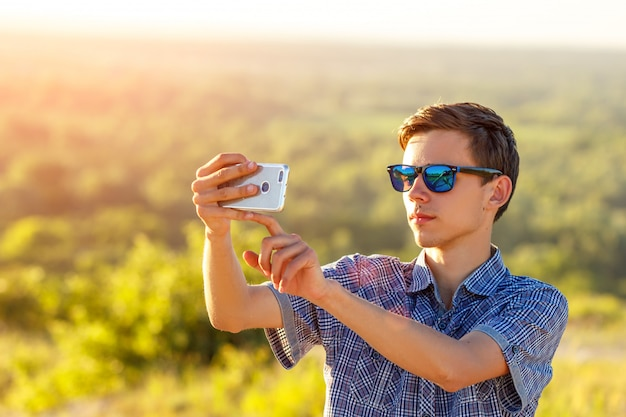 Cute guy takes a selfie on the phone in the sun