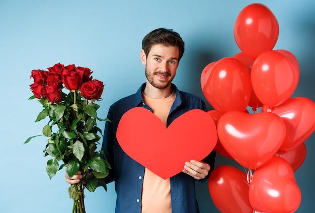 발렌타인 데이와 여자 친구를 기다리는 귀여운 남자 선물, 장미와 붉은 마음의 꽃다발을 들고 카메라에 웃 고, 파란색 배경 위에 서.
