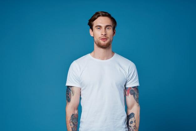 入れ墨と青い背景の上の白いtシャツでリンゴを食べるかわいい男トリミングされたビュー