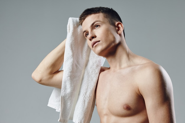 맨손으로 어깨 수건을 손에 들고 땀을 닦는 귀여운 남자
