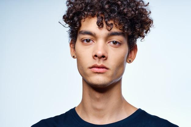 Симпатичный парень с вьющимися волосами, обрезанный вид изолированного фона студии