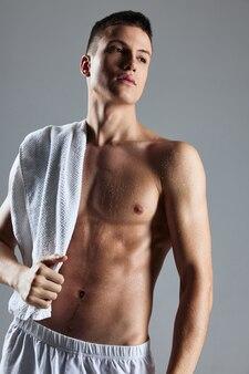白いタオルスタジオをポーズする体をポンプでくむかわいい男。