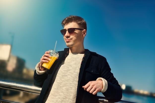 堤防でジュースを保持しているサングラスとかわいい男