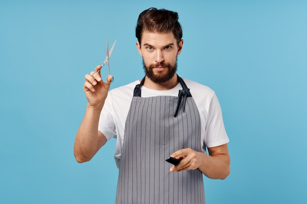 Cute hairdresser with a beard holds scissors and a comb in his hands hairstyle barbershop model