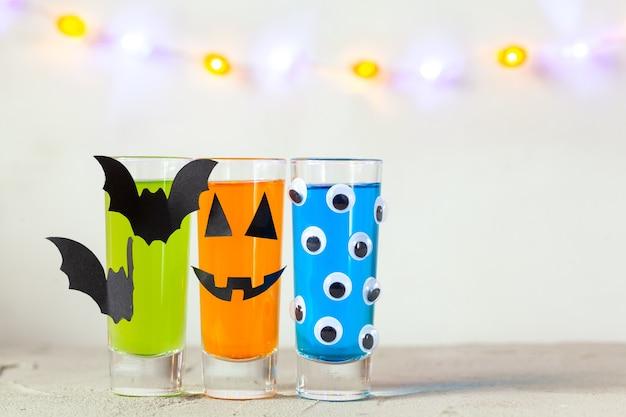 어린이 파티를 위한 귀여운 할로윈 음료. 유리 장식 종이 박쥐와 밝은 배경 복사 공간에 눈에 세 가지 다채로운 주스