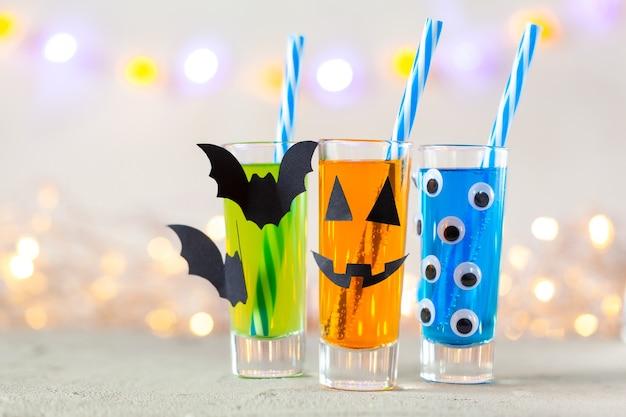 어린이 파티를 위한 귀여운 할로윈 음료. 유리 장식 종이 박쥐에 세 가지 다채로운 주스와 복사 공간이 있는 밝은 배경에 눈