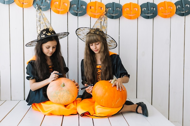 Cute halloween witches drawing on pumpkins