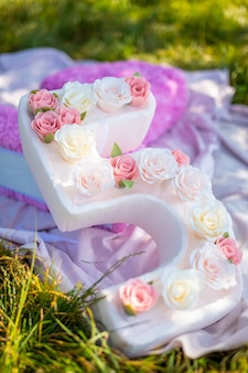 Cute handmade decoration for birthday party big paper number five with flowers in the park