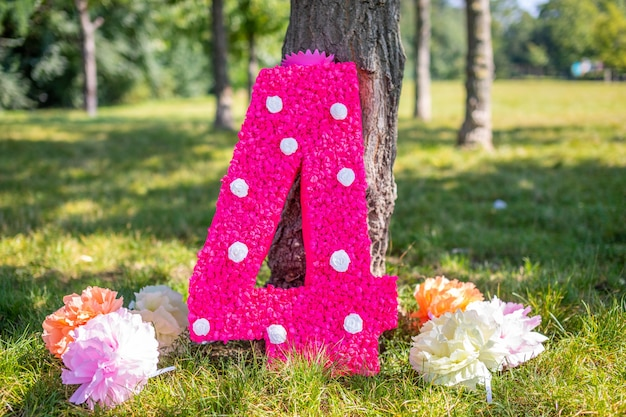 Cute handmade decoration for birthday party big paper number four with flowers in the park