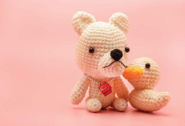 Милый вязаный плюшевый мишка и кукла-утка ручной работы, изолированные на пастельно-розовом фоне с копией пространства