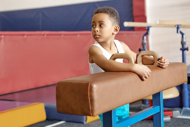 Cute handsome dark skinned schoolboy exercising on pommel horse