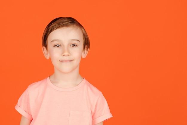 スタジオでポーズをとってかわいいハンサムな笑顔のプレティーンの少年。陽気な少年の肖像画。