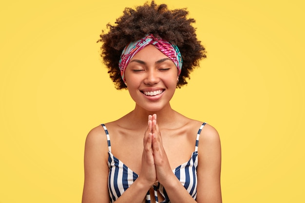 かわいい幸せなアフリカ系アメリカ人の女性は、祈りのジェスチャーで手を保ち、広い笑顔を持ち、重要なイベントの前に祈り、縞模様のtシャツを着て、黄色の壁に向かってポーズをとります。より良く信じる