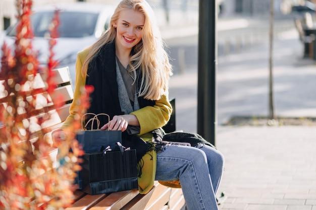 Милая счастливая привлекательная блондинка с пакетами на улице в солнечную теплую погоду
