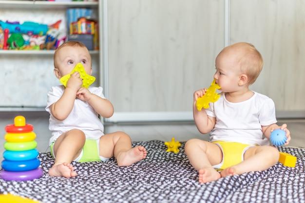 かわいい幸せな赤ちゃんがおもちゃで床で一緒に遊んで、彼らの口にそれらを取ります