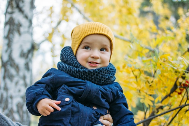 Cute happy baby boy in casual clothes in autumn nature park