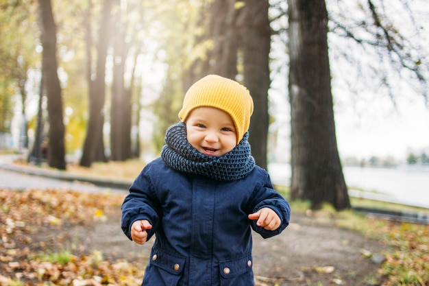 Cute happy baby boy in fashionable casual clothes in autumn nature park